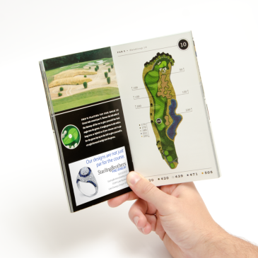 golfer holding a golf course guide book with an advertisement